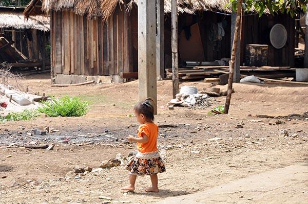 Criança brincando entre as casas de um povoado no Laos
